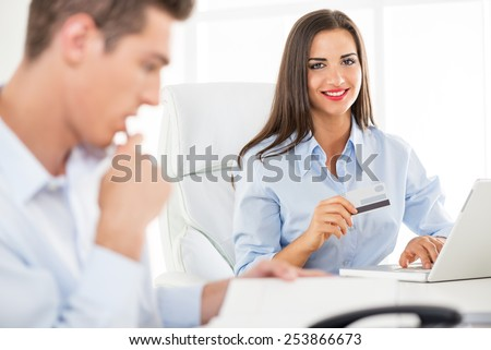 Young business people, woman and man, sitting in an office, a young businesswoman which is in the foreground holding a credit card and with a smile looking at the camera.