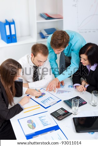 young business people working  on project in team together, men and women discussing the problem, business plan, papers charts, document,  businesspeople meeting sitting at desk office, above top view
