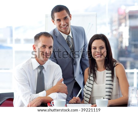Young business people working together in office and smiling at the camera