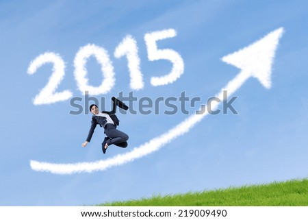 Young business person holding briefcase, jumping on meadow with number 2015 and upward arrow - stock photo