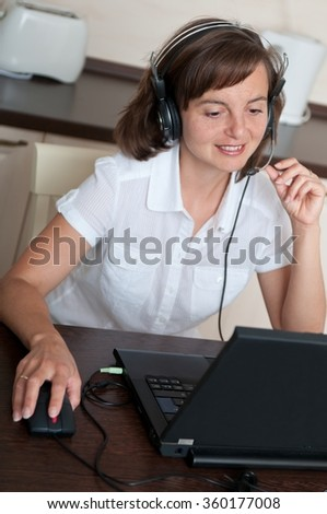 Young business person with headache working at home and calling (headset on head) - stock photo