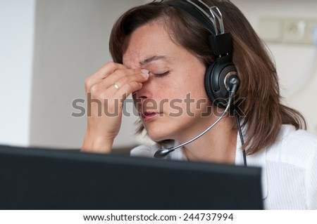 Young business person with headache working with computer(headset on head) - stock photo