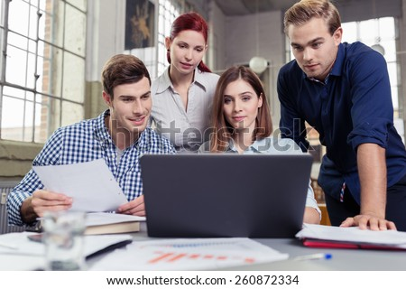 Young business team analysing company data sitting and standing together in a group at a desk with a computer and paperwork having a discussion - stock photo