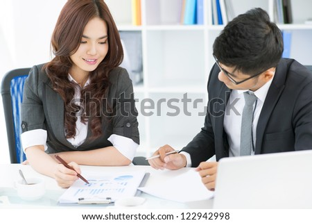 Young business team analyzing statistical data to find the ways of strategic development - stock photo