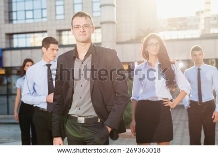 Young business team, elegantly dressed standing outside in front of office building. Looking at camera. - stock photo