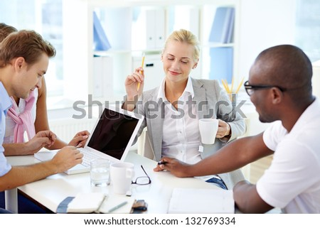 Young business team gathering in office to brainstorm - stock photo