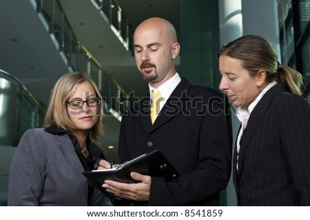 Young business team is looking on schedule - stock photo