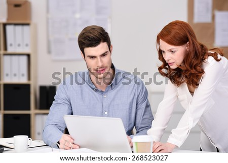 Young business team of a man and woman working together in the office bending over a laptop on a desk discussing information on a laptop computer