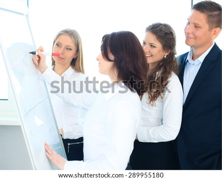 Young business team planning a new strategy standing grouped in front of a flip chart analyzing a chart - stock photo