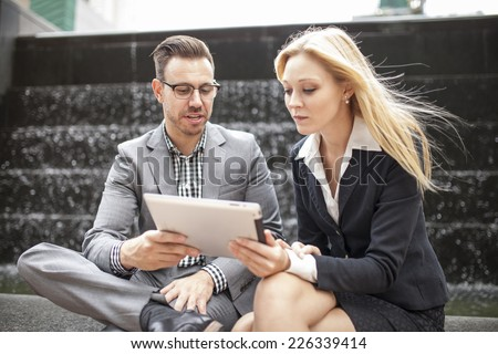 Young business team sitting down together with waterfall behind using tablet - stock photo
