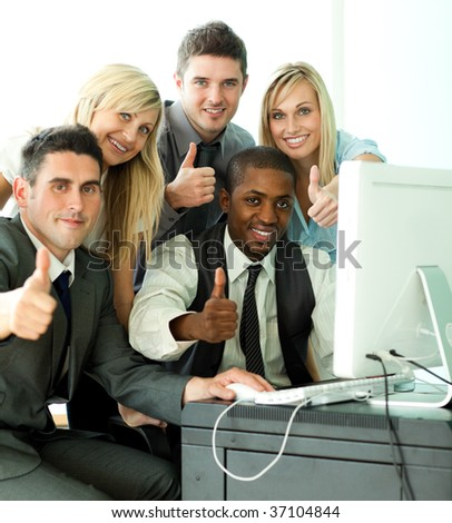 Young business team working in office with thumbs up - stock photo
