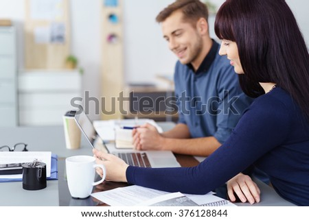 Young business team working on a laptop computer side by side at a desk in the office with focus to the young woman in the foreground in profile - stock photo