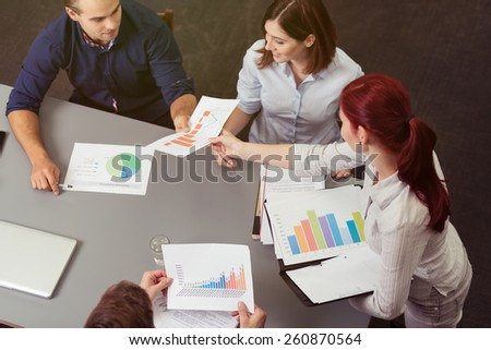 Young business team working on analytical graphs as they sit grouped around a table, high angle view showing the colorful charts