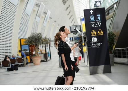 young business travelers man and woman in public transportation station looking for information and schedule - stock photo