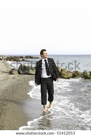 Young business walking along the beach