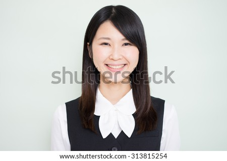 young business woman against light green background