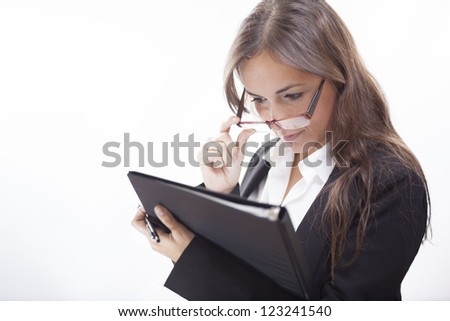 Young business woman analyzing a file while wearing glasses
