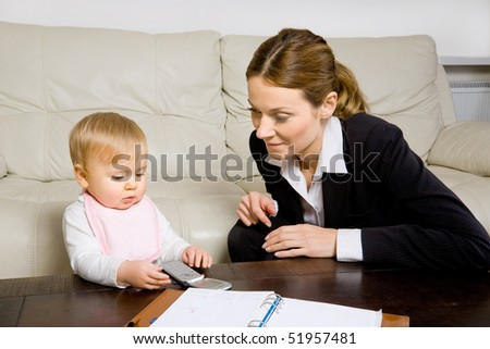 young business woman and her baby girl playing with cell phone - stock photo