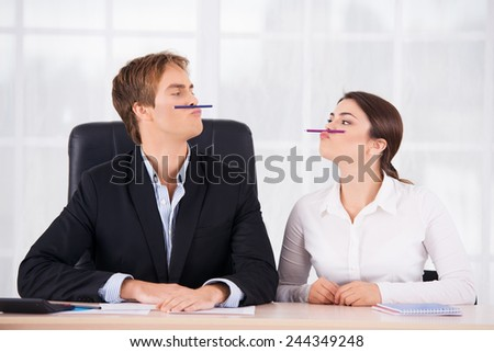 Young business woman and man having fun on working place with pen upper lips - stock photo