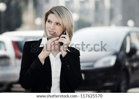 Young business woman calling on the phone against a city traffic - stock photo
