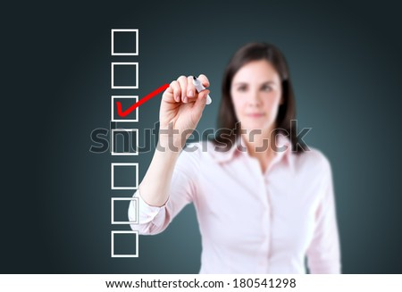 Young business woman checking on checklist box.