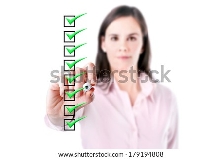 Young business woman checking on checklist boxes, white baclground.  - stock photo