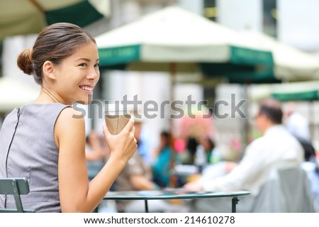 Young business woman coffee break in city park drinking coffee. Happy smiling multiracial young businesswoman in Bryant Park, New York City, USA. - stock photo