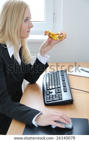 Young business woman concentrating on work and eating pizza