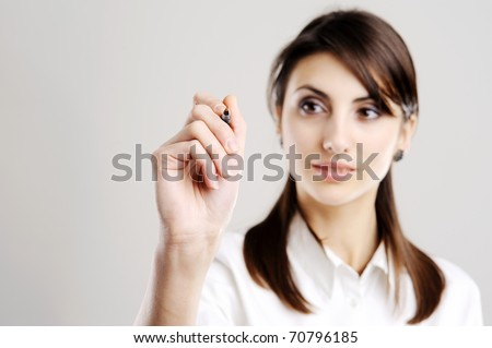 Young business woman drawing on transparent glass - stock photo