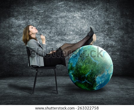 Young business woman dreaming sitting on a chair and put his feet on the globe. - stock photo
