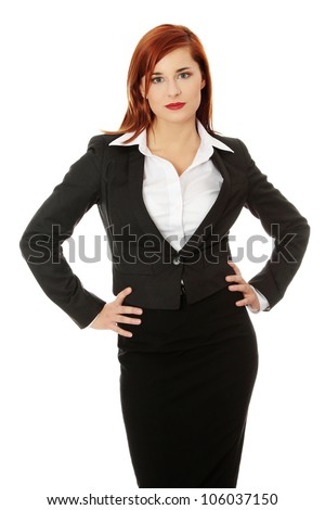 Young business woman dress in black suit and white shirt is standing, looking at you and holding her hands on hips. Long-haired girl is serious and professional. Isolated on the white background. - stock photo