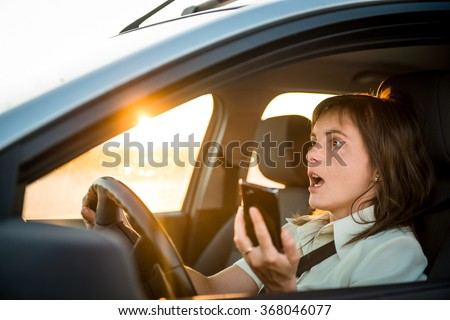 Young business woman drives car with mobile phone in hand - risky driving