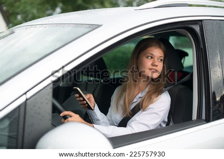 Young business woman driving car and talking on mobile phone (or texting) - stock photo