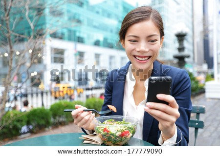 Young business woman eating salad on lunch break in City Park living healthy lifestyle working on smart phone. Happy smiling multiracial young businesswoman, Bryant Park, manhattan, New York City, USA - stock photo