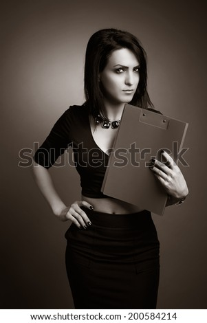 Young business woman, elegantly dressed focuses on the subject, with a clipboard under her chin. Sepia photo version. - stock photo