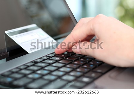 Young business woman  entering  data of  a credit card . On-line shopping on the internet using a laptop