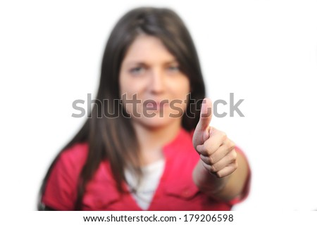 Young business woman gives a thumbs up gesture. Thumb up in focus.