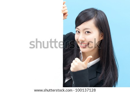 young business woman giving thumbs up with blank billboard, isolated on blue background - stock photo
