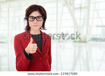 young business woman going thumbs up, at the office - stock photo