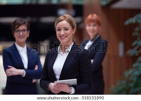 young business woman group,  team standing in modern bright office and working on tablet computer - stock photo