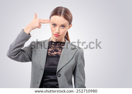 Young business woman hand gun gesturing, isolated on studio background - stock photo