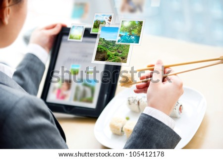 Young business woman having a business lunch at cafe with free wifi internet. She is chatting with her friends using her tablet computer - stock photo