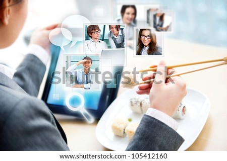 Young business woman having a business lunch at cafe with free wifi internet. She is communicating with her partners using her tablet computer - stock photo