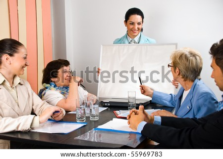 Young business woman holding a blank board and make a presentation at meeting while a senior woman showing with pencil on board