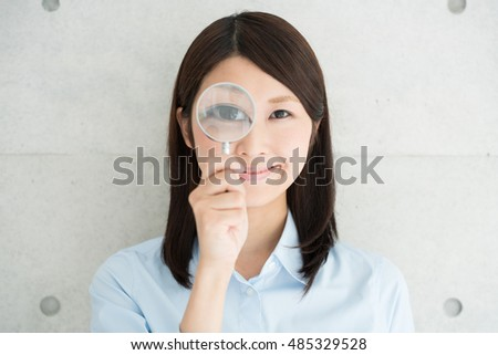 Young business woman holding a magnifying glass
