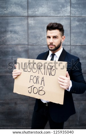 Young business woman holding sign Looking for a job - stock photo