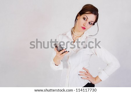 Young business woman holding the cell phone - stock photo