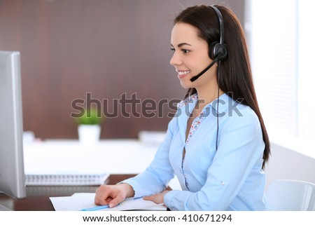 Young business woman in a headset, sitting at the table in the office - stock photo