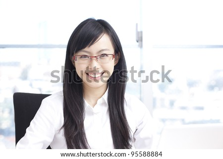 Young business woman in eye glasses working on laptop - stock photo