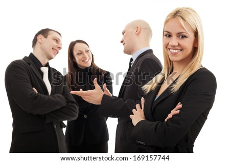 Young business woman in front of a group of business people. Selective focus on blonde business woman - stock photo